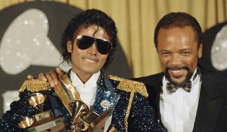 "In this Feb. 28, 1984, file photo, Michael Jackson, left, holds eight awards as he poses with Quincy Jones at the Grammy Awards in Los Angeles. Jackson's estate announced Aug. 7, 2017, that a 3-D version of his iconic ""Thriller"" video will debut at the Venice Film Festival, which begins Aug. 30. (AP Photo/Doug Pizac, File)"