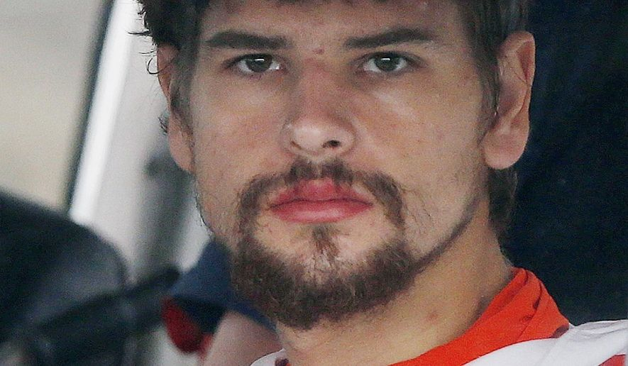 FILE - In this Sept. 27, 2016, file photo, Nathan Carman arrives in a small boat at the US Coast Guard station in Boston after spending a week at sea in a life raft before being rescued by a passing freighter. Carman's boat boat sank with his mother onboard. She was never found. His insurance company is refusing to pay for the loss of the boat, saying his repair work made it unseaworthy. Lawyers for Carman and the insurance company met Monday, Aug. 7, 2017, behind closed doors with a federal magistrate judge in Providence, R.I., to discuss the case. (AP Photo/Michael Dwyer, File)
