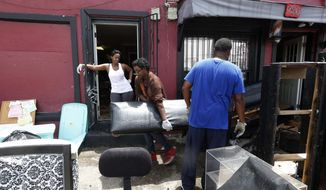 Jomel Walker, center, helps his parents Joann Walker left, and Wallace Walker, throw out soggy furniture from their Crown And Glory Beauty Salon, in the aftermath of the past weekend's flooding, in New Orleans, Monday, Aug. 7, 2017. (AP Photo/Gerald Herbert)