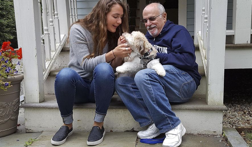 In this photo provided by the Boston Symphony Orchestra, Grace Ellrodt, left, and conductor David Zinman sit with Zinman's puppy Carlito outside his home Monday, Aug. 7, 2017, in Lenox, Mass. Ellrodt found the missing dog Sunday evening after hearing about a plea cellist Yo-Yo Ma made for help following the BSO's matinee concert at Tanglewood. (Hilary Scott/Boston Symphony Orchestra via AP)