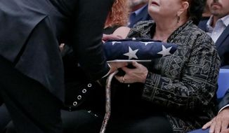 Rebecca Crofts accepts a folded American flag in honor of her father, World War II Staff Sgt. Bernard Snow, during a ceremony recognizing National Purple Heart Day, Monday Aug. 7, 2017, at Federal Hall in New York. The ceremony reunited families with previously lost Purple Hearts belonging to war veterans. (AP Photo/Bebeto Matthews)