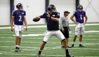 Baltimore Ravens quarterback Ryan Mallett, center, throws a pass in front of quarterbacks Dustin Vaughan (2) and Josh Woodrum (1) during an NFL football training camp practice in Owings Mills, Md., Monday, Aug. 7, 2017. (AP Photo/Patrick Semansky)