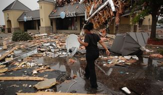 Ahreanna Hytche walks through tornado damage at Highland Plaza to get to work at Schlotzky's in Tulsa, Okla., Monday, Aug. 7, 2017.  (Mike Simons/Tulsa World via AP)