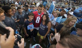 Tennessee Titans quarterback Marcus Mariota (8) poses for pictures before practice at NFL football training camp, at Centennial High School on Friday, Aug. 4, 2017 in Franklin, Tenn. (George Walker IV//The Tennessean via AP)
