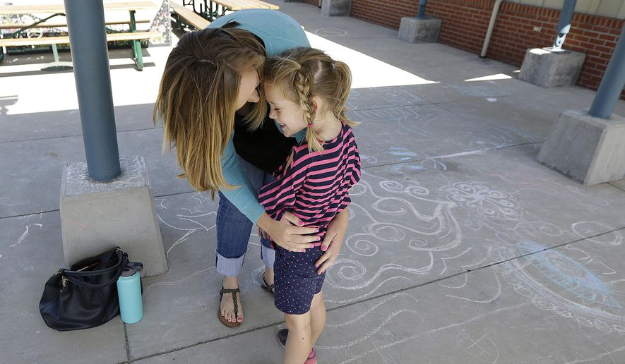 "In this Tuesday, July 11, 2017, photo, Molly Maxwell hugs her child Gracie at the Bay Area Rainbow Day Camp in El Cerrito, Calif. The camp caters to transgender and ""gender fluid"" children, aged 4-12, making it one of the only camps of its kind in the world open to preschoolers, experts say. (AP Photo/Jeff Chiu)"