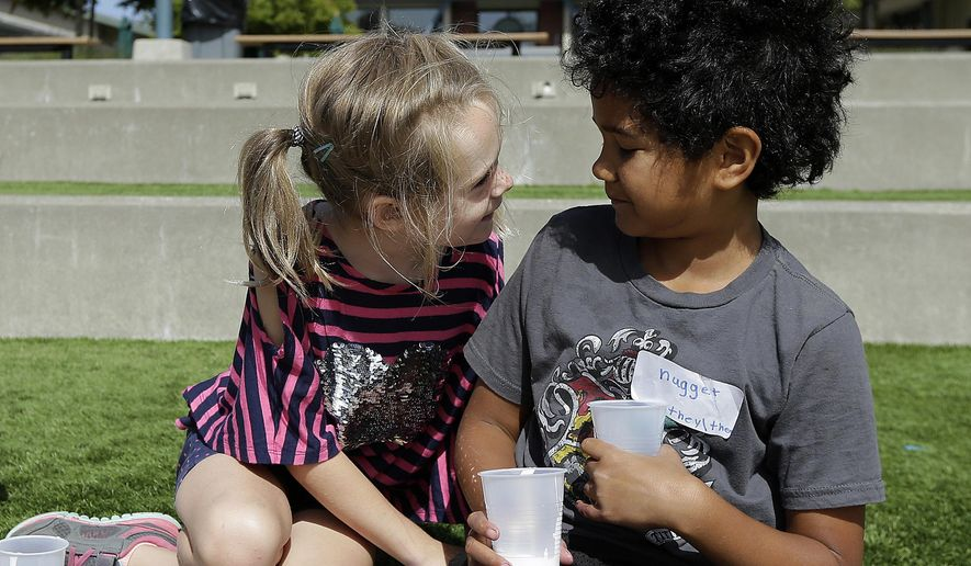 "In this Tuesday, July 11, 2017 photo, campers Gracie, left, leans toward Nugget during an activity at the Bay Area Rainbow Day Camp in El Cerrito, Calif. The camp caters to transgender and ""gender fluid"" children, aged 4-12, making it one of the only camps of its kind in the world open to preschoolers, experts say. Nugget's name tag also includes preferred pronouns. (AP Photo/Jeff Chiu)"
