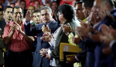"""In this Saturday, Aug. 5, 2017 photo, Venezuela's ombudsman Tarek William Saab, center, is congratulated by members of Constitutional Assembly after he was sworn-in as the nation's new General Prosecutor during the first session of Constitutional Assembly in Caracas, Venezuela. Cries of """"traitor"""" and """"justice"""" erupted from the  salon where pro-government delegates voted unanimously to remove Luisa Ortega from her post as the nation's top law enforcement official and replace her with Saab, a staunch government supporter. (AP Photo/Ariana Cubillos)"""