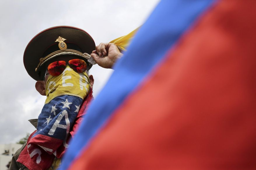 "In this Sunday, Aug. 6, 2017, photo, an anti-government demonstrator wearing a Russian military hat protests the government of Venezuela's President Nicolas Maduro in Caracas, Venezuela. Venezuelan ruling party chief Diosdado Cabello said the military squashed a ""terrorist"" attack at a military base on Sunday, shortly after a small group of men dressed in military fatigues released a video declaring themselves in rebellion. (AP Photo/Wil Riera)"