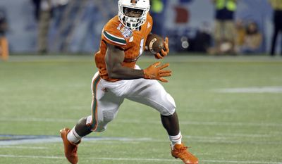 FILE- In this Dec. 28, 2016, file photo, Miami running back Mark Walton (1) runs against West Virginia during the second half of the Russell Athletic Bowl NCAA college football game in Orlando, Fla. Walton was one of the ACC's top rushers last year for the Hurricanes, who are picked to win the ACC's Coastal Division in 2017. (AP Photo/John Raoux, File)