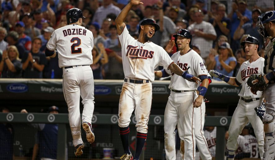Minnesota Twins Brian Dozier celebrates with Byron Buxton, Jason Castro, and Max Kepler, his grand slam against the Milwaukee Brewers in the fourth inning of a baseball game, Tuesday, Aug. 8, 2017, in Minneapolis. (AP Photo/Bruce Kluckhohn)