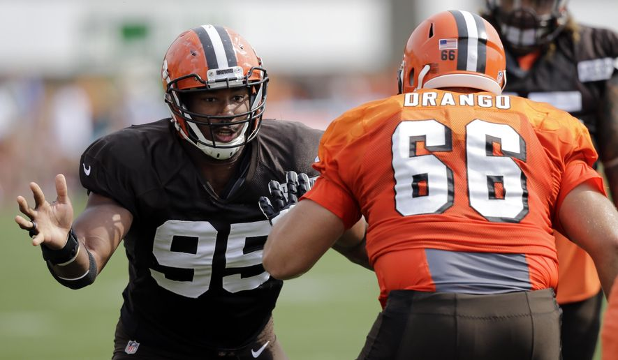Cleveland Browns defensive end Myles Garrett (95) runs through drills with offensive guard Spencer Drango (66) during practice that the NFL football team's training camp facility, Monday, Aug. 7, 2017, in Berea, Ohio. (AP Photo/Tony Dejak)