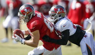 Tampa Bay Buccaneers tight end Cameron Brate (84) makes a catch as cornerback Vernon Hargreaves (28) tackles him during NFL training camp, Tuesday, Aug. 8, 2017 in Tampa, Fla.  (Loren Elliott/Tampa Bay Times via AP)