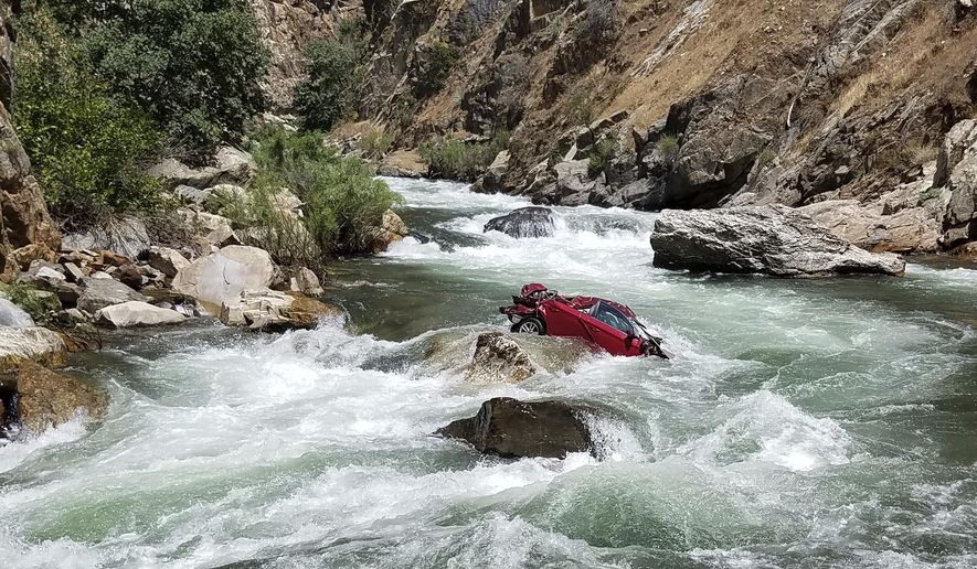 This Aug. 5, 2017, photo provided by the Fresno County Sheriff's office shows a car in the middle of Kings River near Fresno, Calif. The Fresno County Sheriff's Office has been working since July 26 on a plan to remove the car that has two bodies in it. Efforts to remove the car and retrieve the bodies are hampered by rugged terrain. (Fresno County Sheriff's Office via AP)