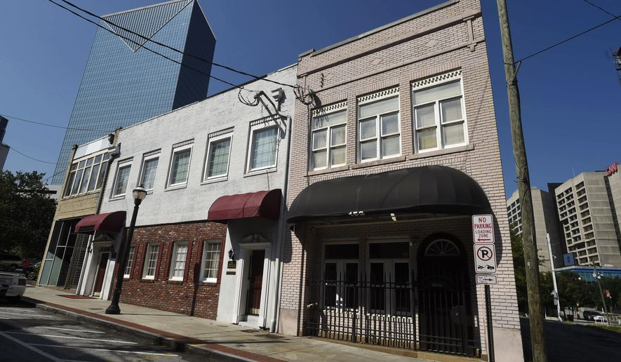 This Wednesday, July 19, 2017, photo shows a two-story brick building, right, at the northwest edge of Atlanta's old downtown. The old building is where the first country music hit was recorded in 1923 by Fiddlin' John Carson. It faces the threat of demolition to make way for a Jimmy Buffett's Margaritaville restaurant. (AP Photo/Mike Stewart)