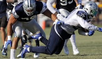 Tyrone Crawford tackles Ezekiel Elliott in football practice as the Dallas Cowboys hold training camp in Oxnard, Calif., Tuesday, Aug. 8, 2017. Crawford badly turned his left ankle making the tackle but there was no immediate word on the severity of the injury. Crawford has started 45 games at end and defensive tackle over the past three seasons since missing all of 2013 after tearing his left Achilles tendon in training camp. (Rodger Mallison/Star-Telegram via AP)