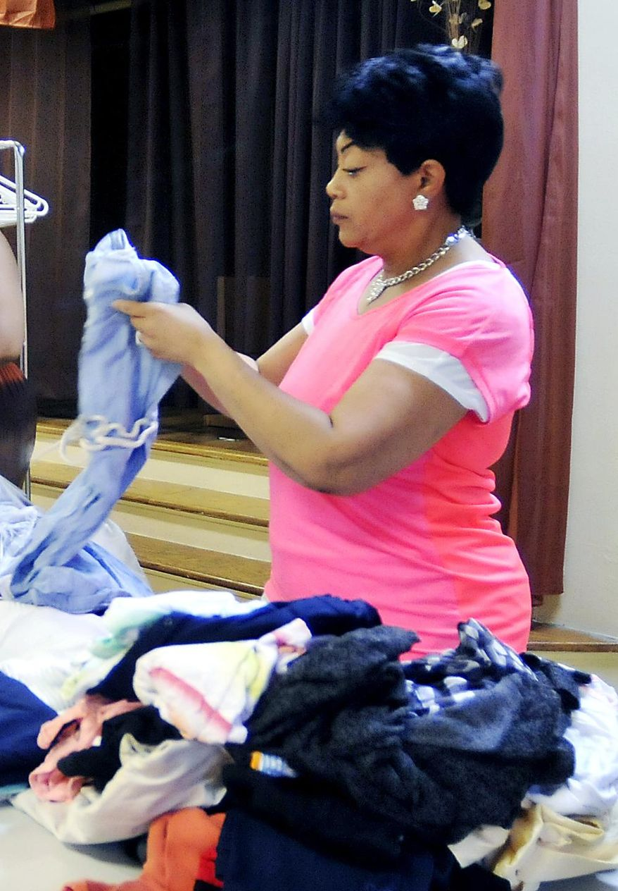 In this July 12, 2017 photo Margie Degraphenreed folds clothes as members of United in Christ Church of Anderson, Ind., prepare for their first monthly dinner and clothes giveaway. The church holds a free community dinner on the second Wednesday of each month as a outreach mission to the people in its neighborhood. (John P. Cleary/The Herald-Bulletin via AP)
