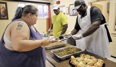 In this July 12, 2017 photo Krista Petersen gets served by Jonathan Jackson, right, as Senior Pastor Louis Jackson Jr., center, looks on during the United in Christ Church's first monthly dinner and clothes giveaway in Anderson, Ind. The church holds the free community dinner the second Wednesday of each month as an outreach mission for those who live in its neighborhood. (John P. Cleary/The Herald-Bulletin via AP)