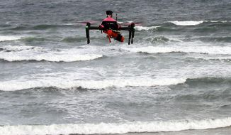 A rescue drone flies during a training flight operation in the Atlantic beach of Biscarrosse, southwestern France, Tuesday, Aug. 8, 2017. A cutting-edge lifesaving initiative is taking flight again this summer off France's popular Atlantic beach destinations: the rescue drone. Following a successful launch in 2016, three airborne life-saver drones are being operated in the southwestern Nouvelle-Aquitaine region spots until September to come to the aid of swimmers struggling in choppy water.(AP Photo/Bob Edme)