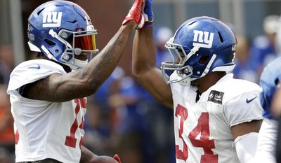 New York Giants wide receiver Brandon Marshall, left, and running back Shane Vereen celebrate after Marshall caught a touchdown pass during a two-minute warning drill during NFL football training camp, Tuesday, Aug. 8, 2017, in East Rutherford, N.J. (AP Photo/Julio Cortez)