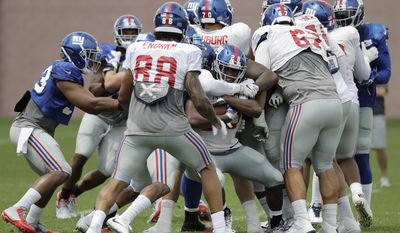 New York Giants running back Paul Perkins, center, is swarmed by teammates while running a play during NFL football training camp, Tuesday, Aug. 8, 2017, in East Rutherford, N.J. (AP Photo/Julio Cortez)