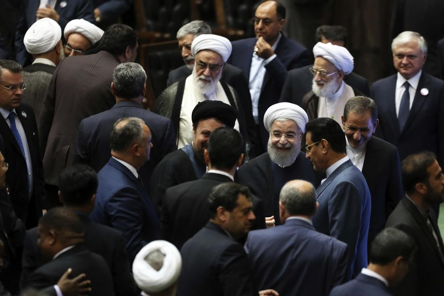 """Iran's President Hasan Rouhani, center, leaves the parliament at the end of his swearing-in ceremony for the second term in office, in Tehran, Iran, Saturday, Aug. 5, 2017. Rouhani, 68, a moderate cleric who secured re-election on May 19, promised that his country will pursue a """"path of coexistence and interaction with the world."""" (AP Photo/Ebrahim Noroozi)"""