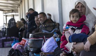 File - In this Sunday, March 26, 2017 file photo, Palestinian residents of Gaza strip wait on the Israeli side of the Erez terminal to cross to Gaza Strip. New Israeli restrictions on Palestinians leaving the blockaded Gaza Strip, include a ban on laptop computers, hard-shell suitcases and even toothpaste. Israel is citing unspecified security concerns as the reason for forcing engineers, journalists, businessmen and human rights workers to leave their electronic work tools behind. (AP Photo/Tsafrir Abayov, File)