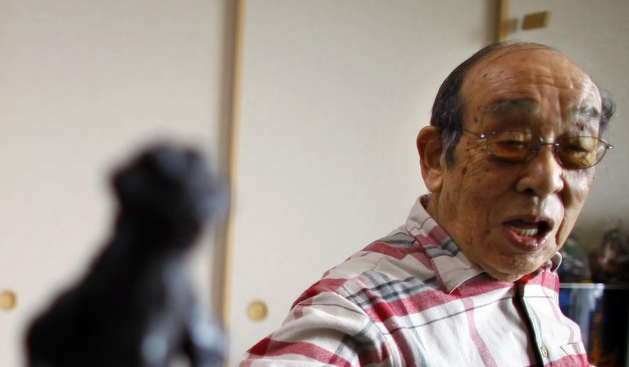 In this April 28, 2014, file photo, original Godzilla suit actor Haruo Nakajima, who has played his role as the monster, points a figure of the monster he made for the movie, as he speaks during an interview at his home in Sagamihara, near Tokyo. Nakajima, the actor who stomped in a rubber suit to portray the original 1954 Godzilla, has died on Monday, Aug. 7, 2017. He was 88. (AP Photo/Junji Kurokawa, File)