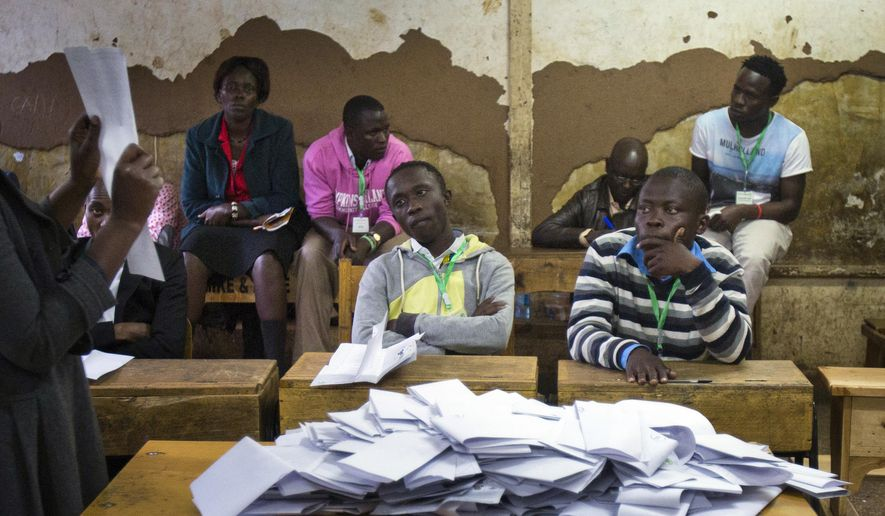 Party observers and election volunteers gather to count the ballots in the Kibera slum in Nairobi, Kenya, Tuesday, Aug. 8, 2017. Kenyans went to the polls to vote in a general election after a tightly-fought presidential race between incumbent President Uhuru Kenyatta and main opposition leader Raila Odinga. (AP Photo/Jerome Delay)
