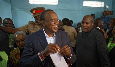 Kenya's President Uhuru Kenyatta smiles as he holds his ballot paper to cast his vote in Gatundu, north of Nairobi, in Kenya Tuesday, Aug. 8, 2017. Kenyans are going to the polls to vote in a general election after a tightly-fought presidential race between incumbent President Uhuru Kenyatta and main opposition leader Raila Odinga. (AP Photo/Ben Curtis)