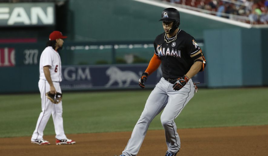 Miami Marlins' Giancarlo Stanton (27) rounds third after hitting a three run homer at Washington Nationals third baseman Anthony Rendon (6) stands in the background during the fifth inning of baseball game, Tuesday, Aug. 8, 2017, in Washington. (AP Photo/Carolyn Kaster)