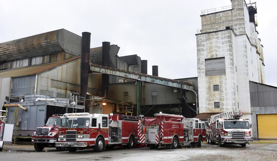 In this Monday, Aug. 7, 2017 photo, fire trucks sit at the Owens-Illinois glass plant in Zanesville, Ohio. Authorities said tons of molten glass spilled from a ruptured tank at the Ohio plant, oozing like lava from a small hole that quickly grew several feet wide. (Chris Crook/Times Recorder via AP)