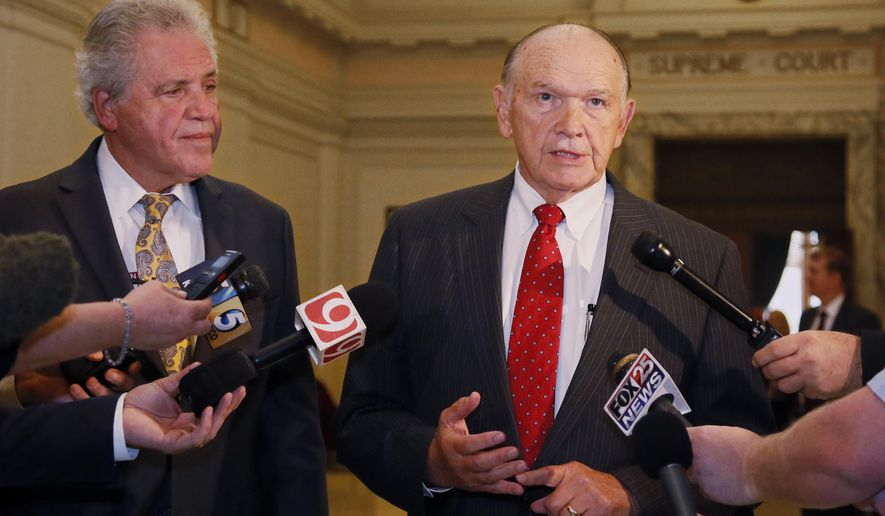 Attorney Stan Ward, right, talks with the media following oral arguments before the Oklahoma's Supreme Court in connection with three lawsuits that challenge revenue-raising measures adopted by lawmakers in Oklahoma City, Tuesday, Aug. 8, 2017. Looking on at left is Gary Richardson. (AP Photo/Sue Ogrocki)