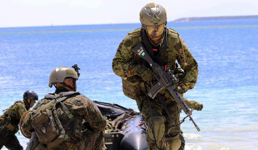 "FILE - In this May 13, 2017 file photo, Japanese soldiers use rubber rafts as part of an amphibious drill during joint military exercises between the U.S., Japan, France and the United Kingdom, on Naval Base Guam. North Korea says it is examining its operational plans for attacking Guam to contain U.S. bases there. The army said in a statement distributed Wednesday, Aug. 9 by the state-run news agency that it is studying a plan to create an ""enveloping fire"" in areas around Guam with medium- to long-range ballistic missiles. The U.S. territory is home to Andersen Air Force Base.  The statement says the move is in response to a recent U.S. ICBM test. (AP Photo/Haven Daley, File)"