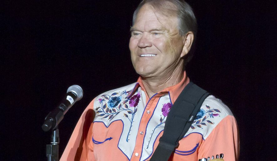 "FILE - This Sept. 6, 2012 file photo shows singer Glen Campbell performing during his Goodbye Tour in Little Rock, Ark. Campbell, the grinning, high-pitched entertainer who had such hits as ""Rhinestone Cowboy"" and spanned country, pop, television and movies, died Tuesday, Aug. 8, 2017. He was 81. Campbell announced in June 2011 that he had been diagnosed with Alzheimer's disease. (AP Photo/Danny Johnston, File)"