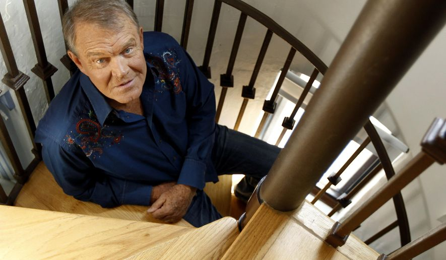"In this July 27, 2011 photo, musician Glen Campbell poses for a portrait in Malibu, Calif. Campbell, the grinning, high-pitched entertainer who had such hits as ""Rhinestone Cowboy"" and spanned country, pop, television and movies, died Tuesday, Aug. 8, 2017. He was 81. Campbell announced in June 2011 that he had been diagnosed with Alzheimer's disease. (AP Photo/Matt Sayles, File)"
