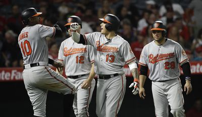 Baltimore Orioles' Manny Machado, center, celebrates his grand slam as he walks off the field with Adam Jones, from left, Seth Smith and Welington Castillo during the seventh inning of a baseball game, Monday, Aug. 7, 2017, in Anaheim, Calif. (AP Photo/Jae C. Hong)