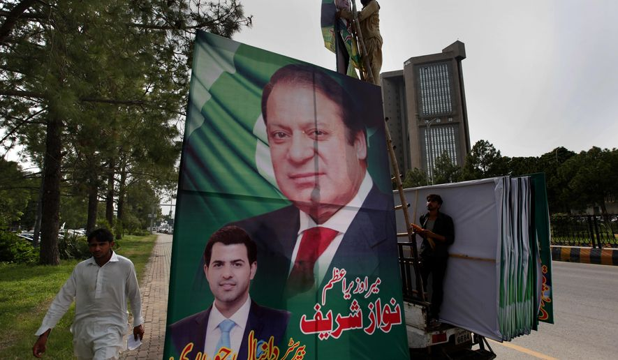 Pakistani workers install a huge billboard of deposed Prime Minister Nawaz Sharif on the planned route of his rally at a highway in Islamabad, Pakistan, Tuesday, Aug. 8, 2017. According to Malik Mohammad Ahmed, a spokesman in Punjab where Lahore is the provincial capital, Sharif planned to travel with a convoy of supporters by road on Wednesday from the capital, Islamabad, to Lahore. (AP Photo/ Anjum Naveed)