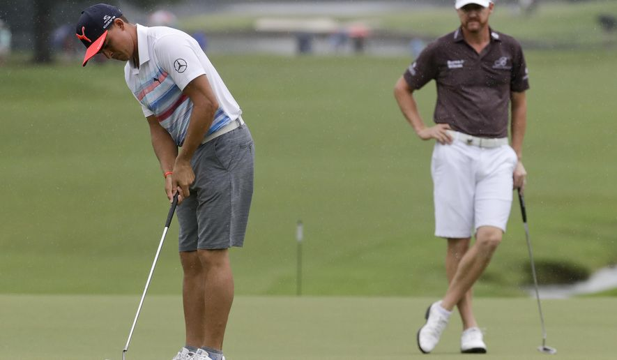 Rickie Fowler, left, putts as Jimmy Walker watches on the 18th hole during a practice round for the PGA Championship golf tournament at the Quail Hollow Club Tuesday, Aug. 8, 2017, in Charlotte, N.C. For the first time, the PGA Championship is letting players wear shorts in practice rounds. (AP Photo/Chris Carlson)