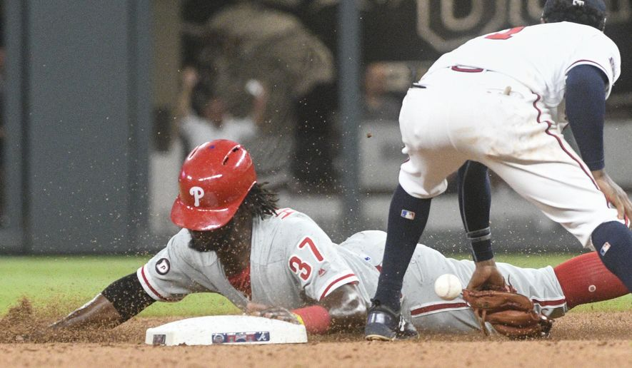 Philadelphia Phillies' Odubel Herrera (37) steals second base as Atlanta Braves second baseman Ozzie Albies can't glove the throw from catcher Kurt Suzuki during the fourth inning of a baseball game, Tuesday, Aug. 8, 2017, in Atlanta. (AP Photo/John Amis)