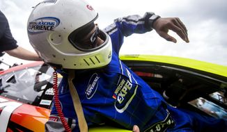 Washington Redskins cornerback Josh Norman squeezes out of Dale Earnhardt Jr.'s car after being driven around the track, Tuesday Aug. 8, 2017 in Richmond, Va. (Shaban Athuman/Richmond Times-Dispatch via AP)