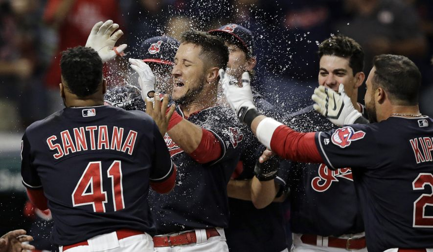 Cleveland Indians' Yan Gomes, center, is mobbed by teammates after Gomes hit a game-winning three-run home run off Colorado Rockies relief pitcher Greg Holland in the ninth inning of a baseball game, Tuesday, Aug. 8, 2017, in Cleveland. The Indians won 4-1. (AP Photo/Tony Dejak)