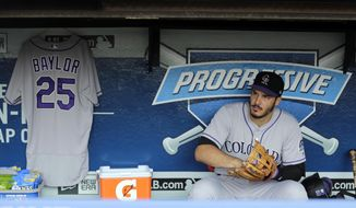 Colorado Rockies' Nolan Arenado sits by former Rockies manager Don Baylor's jersey hanging in the visitor's dugout before the Rockies play the Cleveland Indians in a baseball game, Tuesday, Aug. 8, 2017, in Cleveland. (AP Photo/Tony Dejak)