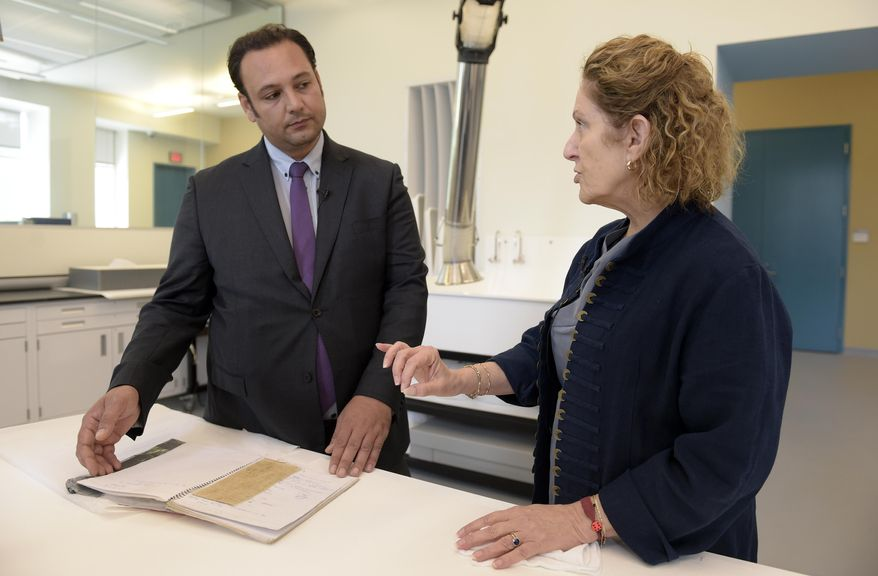 Jane Klinger, right, chief conservator for the United States Holocaust Memorial Museum, talks with Mansour al-Omari, left, a Syrian human-rights activist documenting cases of people who have disappeared under President Bashar Assad's government, who shows scraps of fabric with the names of fellow inmates he is presenting to the U.S. Holocaust Memorial Museum for preservation at the conservation center, Tuesday, Aug. 8, 2017, in Bowie, Md.  (AP Photo/Susan Walsh)