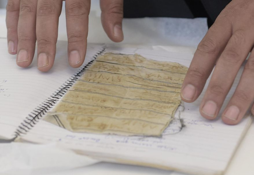 Mansour al-Omari, a Syrian human-rights activist documenting cases of people who have disappeared under President Bashar Assad's government, shows scraps of fabric with the names of fellow inmates he is presenting to the U.S. Holocaust Memorial Museum for preservation at the conservation center, Tuesday, Aug. 8, 2017, in Bowie, Md. (AP Photo/Susan Walsh)