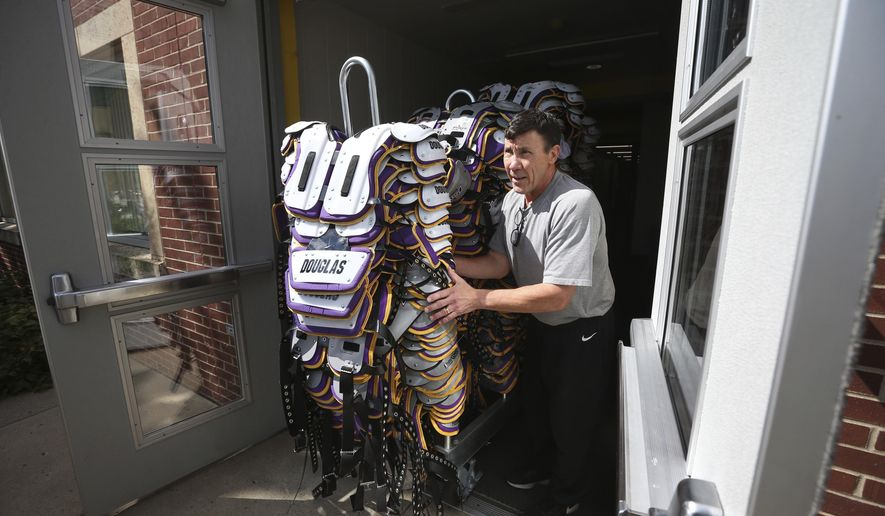 In this Monday, Aug. 7, 2017 photo, Minnesota Vikings equipment manger Dennis Ryan pushes a stack of shoulder pads to a truck as the team prepared to leave Minnesota State University after 52 years in Mankato, Minn. (Jerry Holt/Star Tribune via AP)