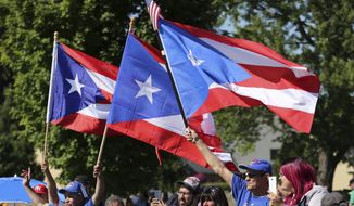Fans wave flags of Puerto Rico as compatriot Ivan Rodriguez speaks during his induction into the National Baseball Hall of Fame in Cooperstown, N.Y., Sunday, July 30, 2017. (AP Photo/Reed Saxon)