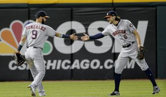 Houston Astros center fielder Jake Marisnick (6) congratulates left fielder Marwin Gonzalez after Gonzalez threw out Chicago White Sox's Leury Garcia at home during the seventh inning of a baseball game, Tuesday, Aug. 8, 2017, in Chicago. (AP Photo/Charles Rex Arbogast)