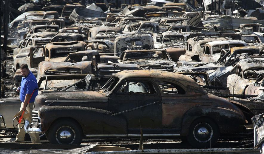 An insurance company investigator walks around the front of a 1940's era car Wednesday, Aug. 9, 2017, at Country Classic Cars on Interstate-55 near the town of Staunton, Illinois. A fire, which broke out late Tuesday night, destroyed perhaps as many as 100 classic antique cars which were housed in two buildings on the property. (John Badman /The Telegraph via AP)