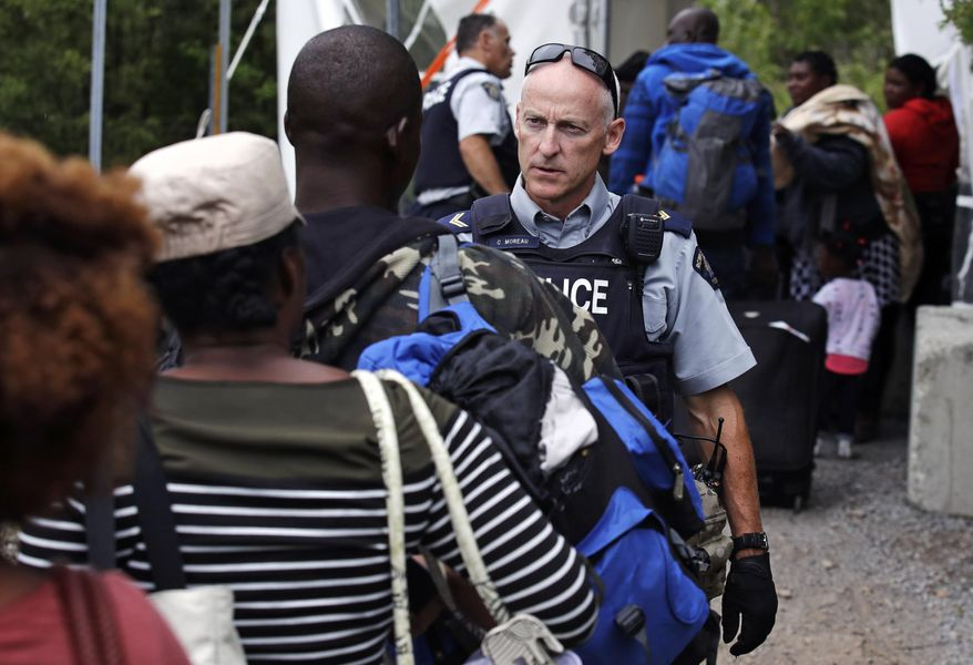 A Royal Canadian Mounted Police officer standing in Saint-Bernard-de-Lacolle, Quebec, advises migrants that they are about to illegally cross from Champlain, N.Y., and will be arrested, Monday, Aug. 7, 2017. Officials on both sides of the border first began to notice last fall, around the time of the U.S. presidential election, that more people were crossing at Roxham Road. Since then the numbers have continued to climb. (AP Photo/Charles Krupa)