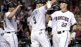 Arizona Diamondbacks' Jake Lamb (22) celebrates with Chris Iannetta (8) and A.J. Pollock (11) after hitting a grand slam during the seventh inning of a baseball game against the Los Angeles Dodgers, Tuesday, Aug. 8, 2017, in Phoenix. (AP Photo/Matt York)
